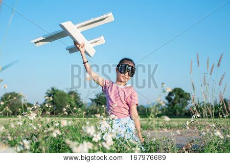 Asian Girl Dressed As Pilot Playing Airplane Toy At Grass Flower Paddy Field.