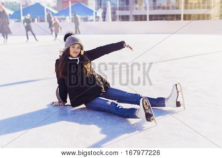Ice Skating Woman Sitting On The Ice Rink. Unsuccessful Attempt