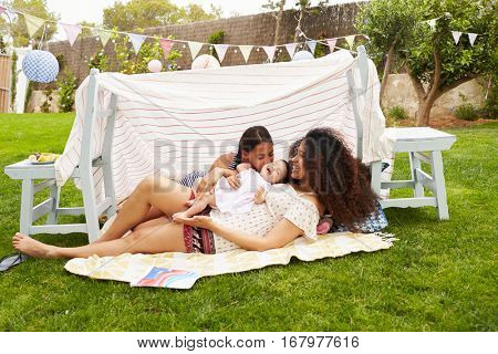 Mother Playing With Daughters In Home Made Garden Den