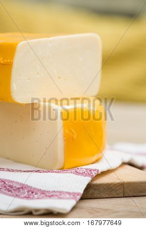 Two big organic cheese heads in yellow vacuum package laying on top of each other in the farm kitchen. Food concept