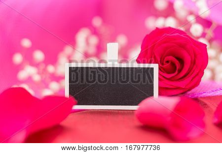 Closeup Of Blank Blackboard Sign With Red Rose And Petals, On Pink Background And Copy-space.