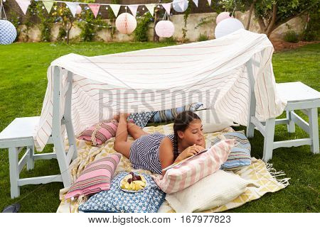 Girl Reading Book and Eating Snack In Home Made Garden Den