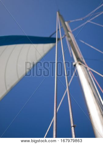 Yacht mast and sail with a blue sky backdrop