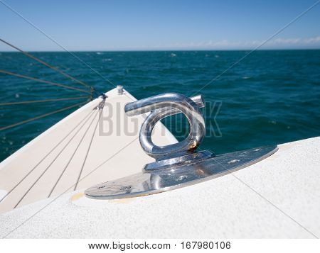 Metal rope anchor point on a yacht boat with a green sea and blue sky backdrop