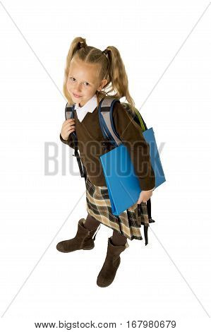 young beautiful blond schoolgirl with pigtails and school uniform carrying backpack and folder posing cheerful and happy isolated on white background in child education concept