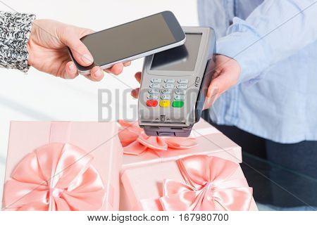 Making contactless payment for a gifts with smart phone over payment terminal at shop