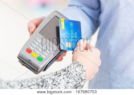 Hand holding contactless credit or debit card over wireless payment terminal at shop