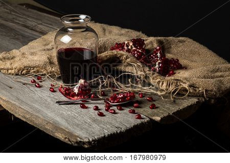 Carafe with pomegranate juice seeds with a spoon on a wooden table.