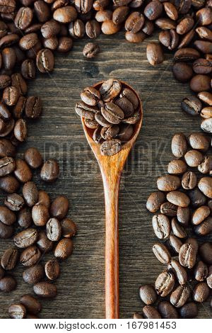 Top View Of Wood Teaspoon Filled With Coffee Beans Rounded With Coffee Seeds Over The Woodeen Backgr