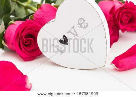 White Wooden Heart With Word Love On It And A Bouquet Of Red Roses And Petals