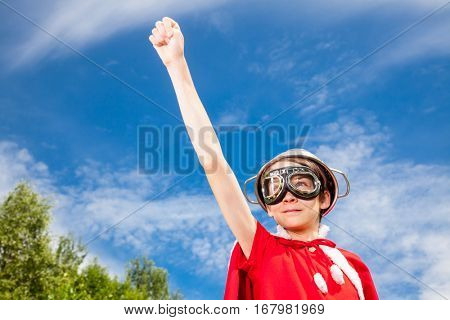 Low angle view of cute teen boy wearing metal colander as a helmet goggles and red costume - a funny power super hero child concept