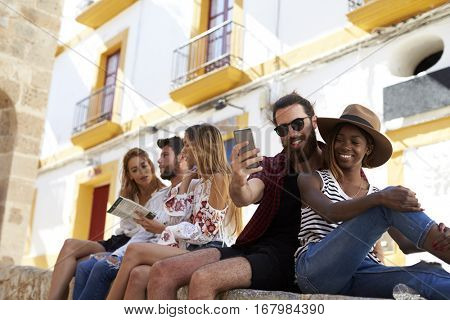 Friends sit on wall reading a guidebook and taking selfies