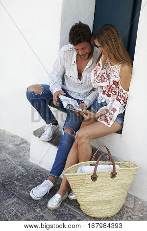 Young couple sitting on steps looking at a guidebook, Ibiza