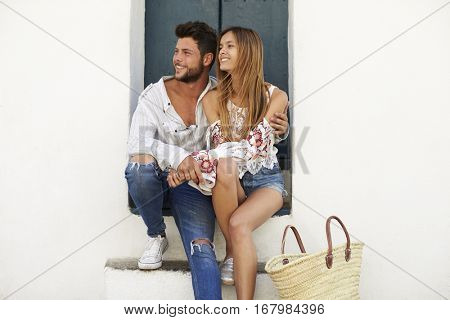 Happy couple sitting in a doorway looking away, Ibiza, Spain