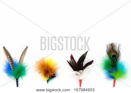 Colorful handmade feather cat toys as attachment for teaser wand and rod. On white background with lots of copy space.