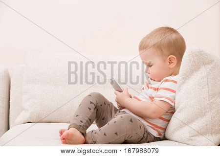 Adorable toddler boy sitting on the sofa in the living room and playing with smartphone. Child learning how to use smartphone. Boy texting on the phone. - technology and lifestyle concept