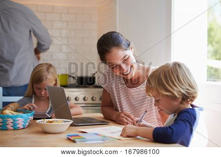 Kids doing homework at kitchen table with mum, close up