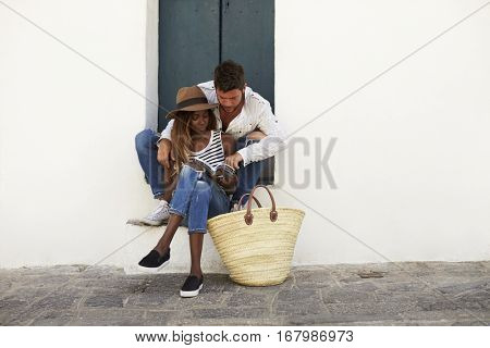 Adult couple sitting on steps looking at a guidebook, Ibiza