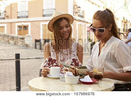 Two female friends reading a guidebook outside a cafe, Ibiza