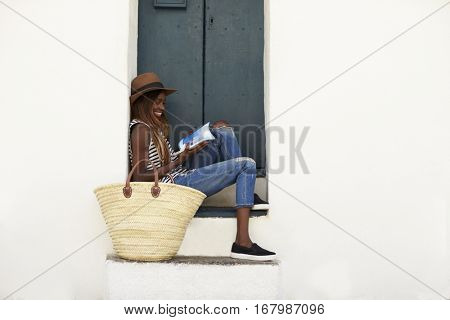 Young woman on holiday sitting on steps reading a guidebook