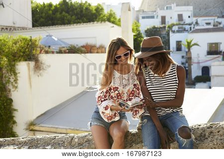 Two female friends sitting on wall reading guidebook, Ibiza