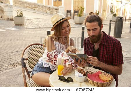 Couple sitting and reading guidebook in coffee shop, Ibiza, Spain