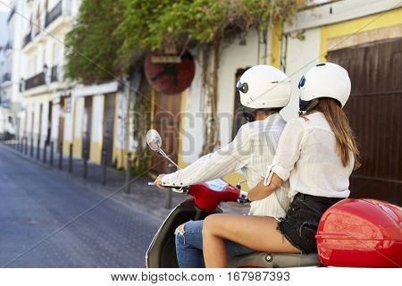 Young adult couple on a motor scooter in a street, Ibiza