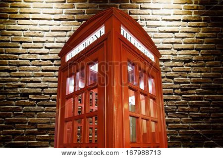 red telephone booth against illuminated brick wall