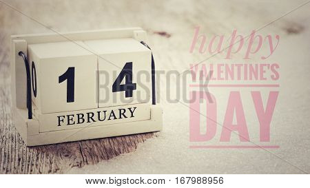 February 14 on wooden cube calendar on wood table with snow background vintage style