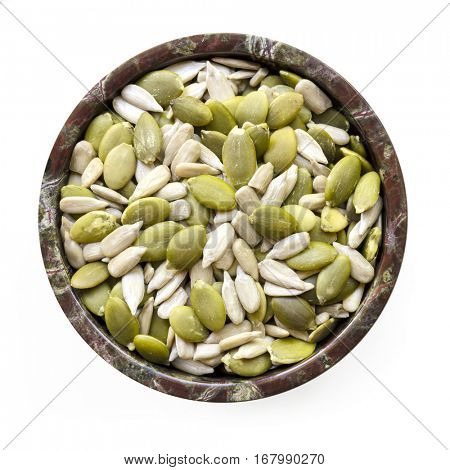 Sunflower and pumpkin seeds or pepitas in small stone bowl.  Top view, isolated with soft shadow.  Healthy eating.