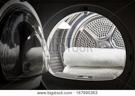 Stacked clean white towels inside washing machine drum. Clean concept. Laundry. Closeup of open washing machine.
