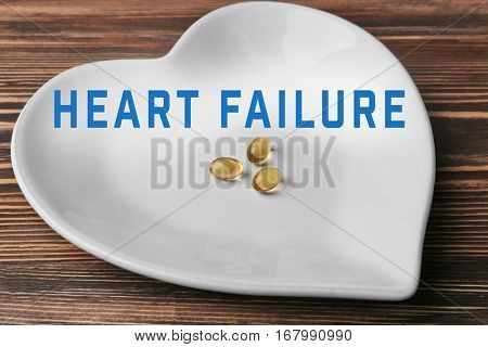 Cardiology and health care concept. Heart shaped plate with cod liver oil capsules on wooden table