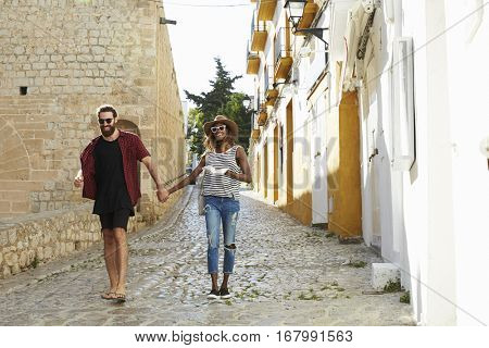 Couple on holiday walking in Ibiza streets with a guidebook