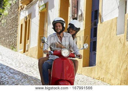 Couple riding motor scooter in old Ibiza street, close up