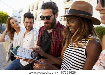 Friends on vacation in Ibiza looking at a guidebook, close up