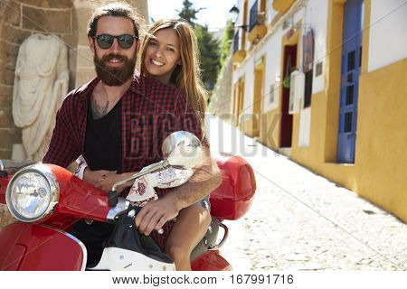 Couple sitting on motor scooter, looking to camera, Ibiza