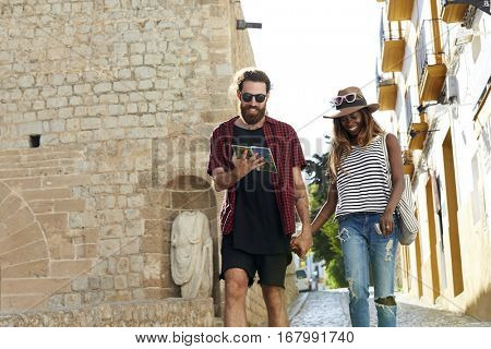 Couple on holiday walk, reading a guidebook, three quarters