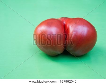 Tomato with sexy form resembling woman ass on green table