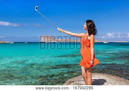 Pretty young woman dressed in a coral clothes having fun making selfie with a selfiestick on the background of the azure sea