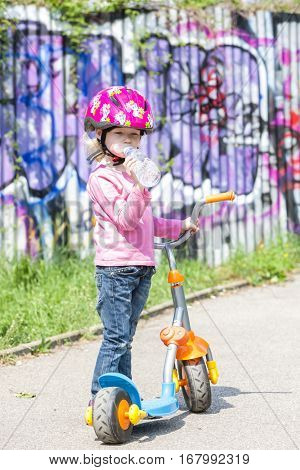 little girl with a scooter drinking water