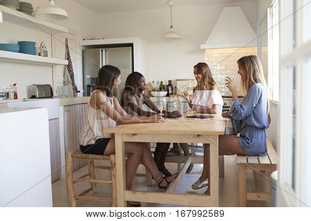 Four women at kitchen table with wine during girlsâ?? night in