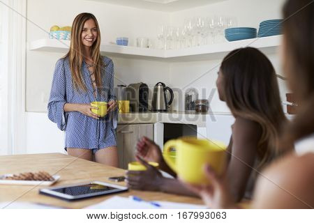 Three female friends drinking coffee in the kitchen, Ibiza