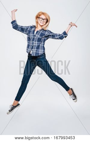 Picture of an attractive lady wearing eyeglasses jumping isolated on a white background and holding copyspace in hand.