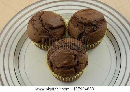 Three sugarless chocolate chip chocolate muffins or cupcakes without frosting on plate