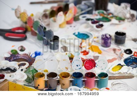 Top view on painting set of brushes paints watercolor acrylic paint on a white background. Set of brushes and paints on the table in the daycare. Children's art table at home.