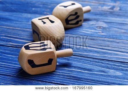 Dreidels for Hanukkah on blue wooden table, close up
