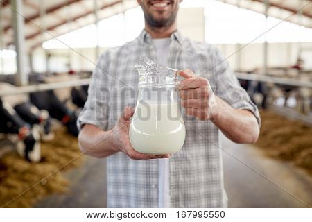 agriculture industry, farming, people and animal husbandry concept - happy smiling young man or farmer with cows milk in jug at cowshed on dairy farm