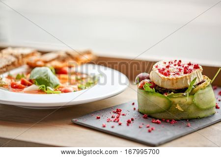 food, culinary, haute cuisine and cooking concept - goat cheese salad with vegetables and dried raspberries and plate of gazpacho soup at restaurant or cafe