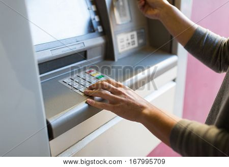 finance, money, bank and people concept - close up of hand entering pin code at atm machine