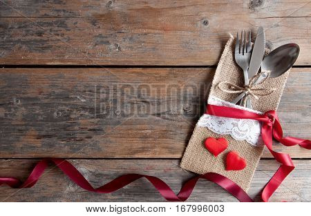 Valentines day cutlery set inside pouch with red hearts and silk ribbon over a wooden background